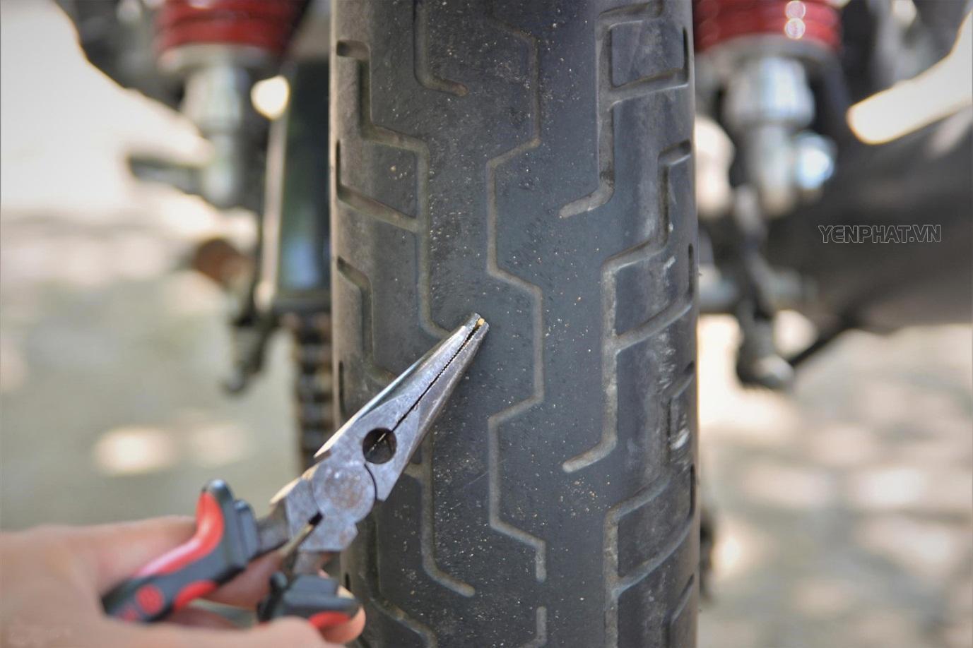 Dùng kìm lấy hết các dị vật gây thủng lốp xe